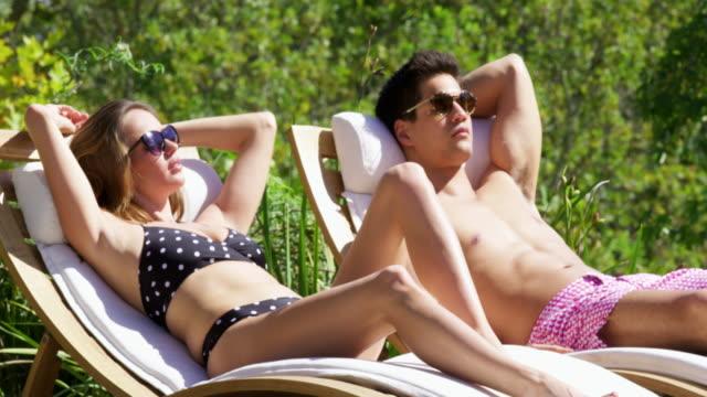 couple sunbathing - solstol bildbanksvideor och videomaterial från bakom kulisserna