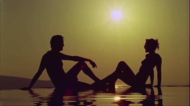 vídeos de stock, filmes e b-roll de ws couple sunbathing while rippled water reflects their shadows / santorini, greece - lago infinito