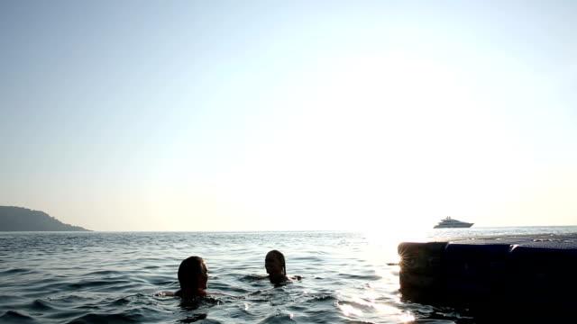 Couple swim in sea next to pier, sunrise
