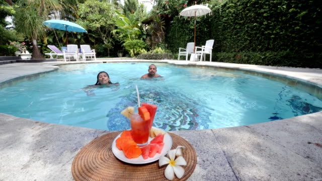 couple swims towards a healthy snack and drink and eat in a luxury spa villa in bali - military private stock videos & royalty-free footage