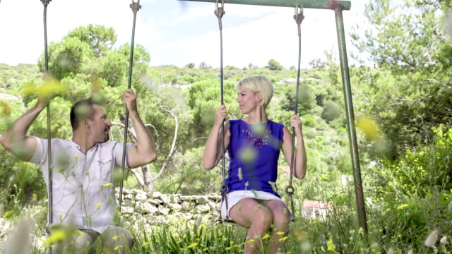 slo mo ds couple swinging on a swing - mid adult couple stock videos & royalty-free footage