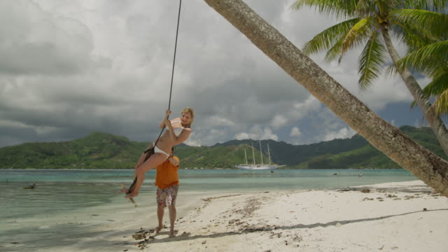 couple swinging on the beach - isola di tahaa video stock e b–roll