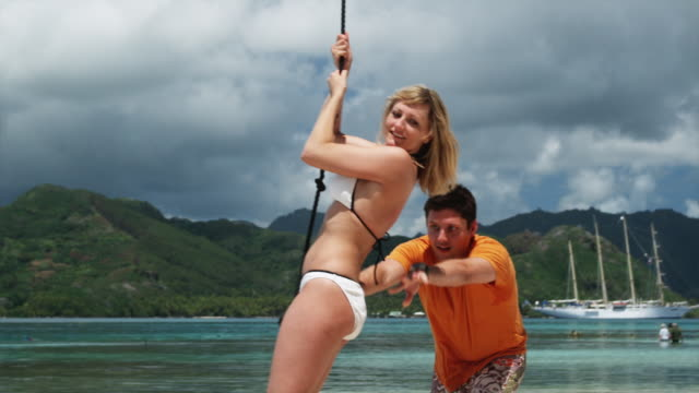 couple swinging on the beach - tahaa island stock videos & royalty-free footage