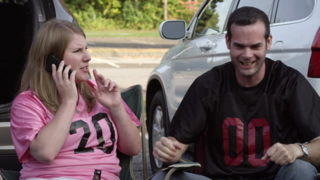 couple tailgating and watching a sporting event - shirt stock videos & royalty-free footage