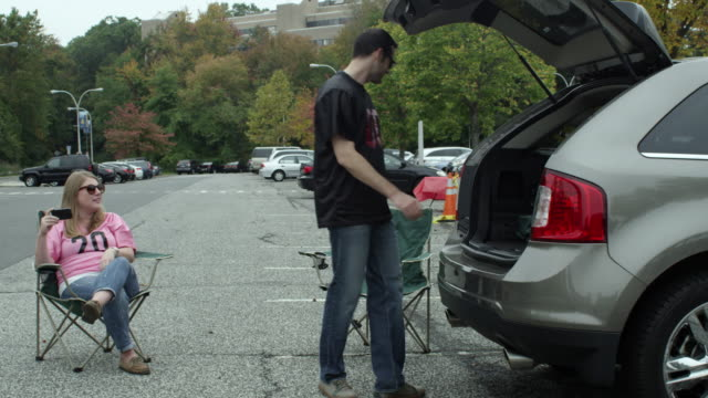 couple tailgating in parking lot - shirt stock videos & royalty-free footage