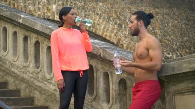 vídeos y material grabado en eventos de stock de a couple take a break after a workout to drink water. - slow motion - pareja de mediana edad