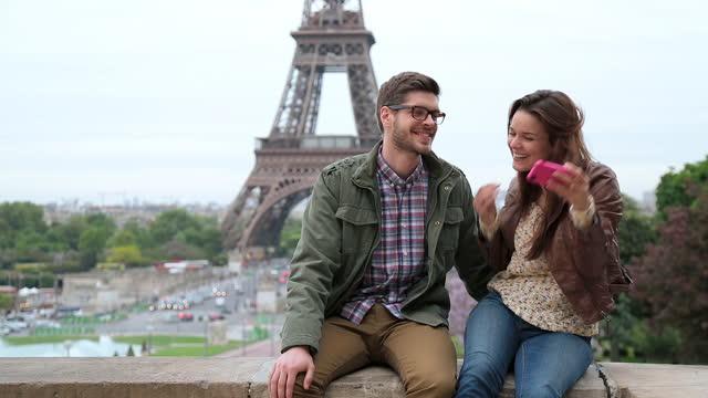 A couple take a photo near the Eiffel Tower.