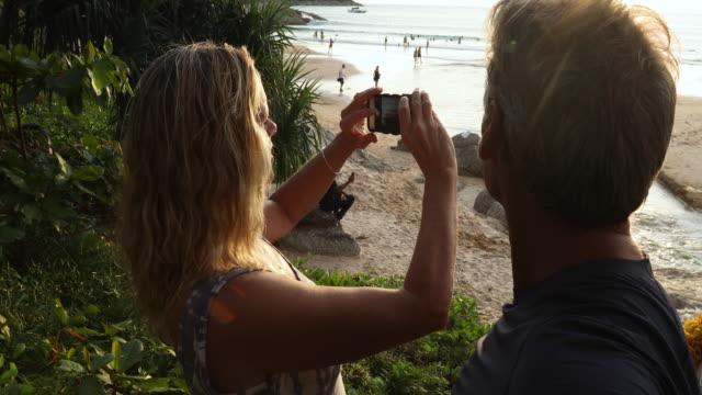 couple take pic as sun sets over beach - meraviglie della natura video stock e b–roll