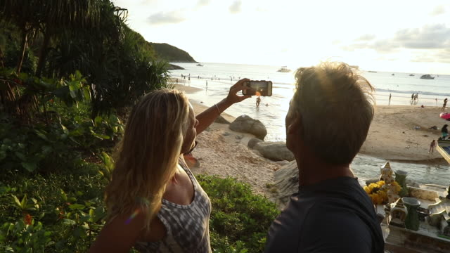 couple take pic near shrine as sun sets over beach - プーケット県点の映像素材/bロール