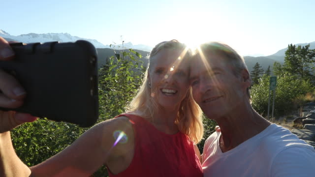 Couple take selfie at beautiful mountain overlook