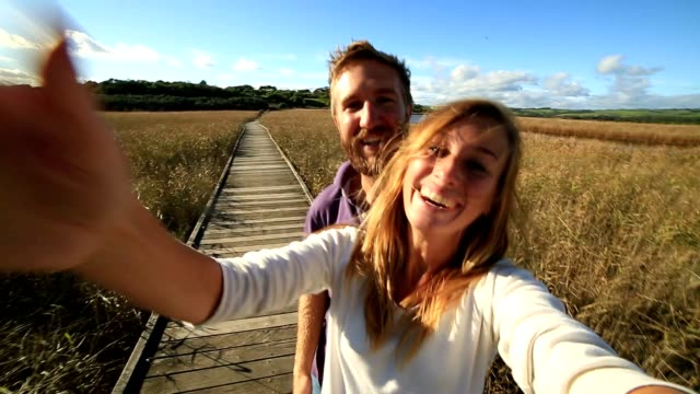 Couple take selfie in wheat meadow