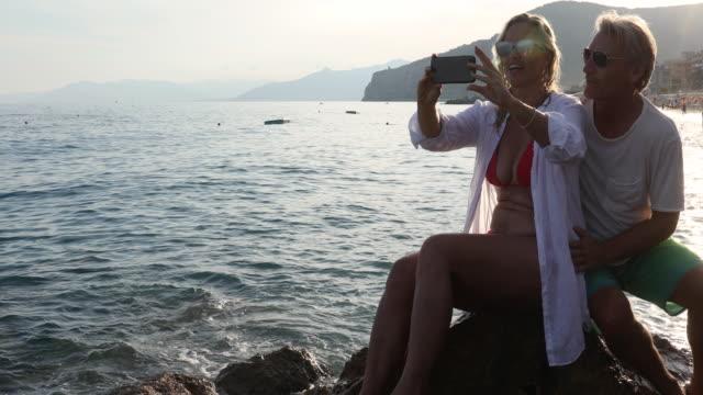 vídeos y material grabado en eventos de stock de par toma selfie en roca sobre el mar al amanecer - pareja madura