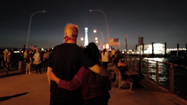 couple takes a moment of reflection during a 9/11 community vigil at the american veterans memorial pier on september 11, 2020 in bay ridge,... - 追悼行事点の映像素材/bロール