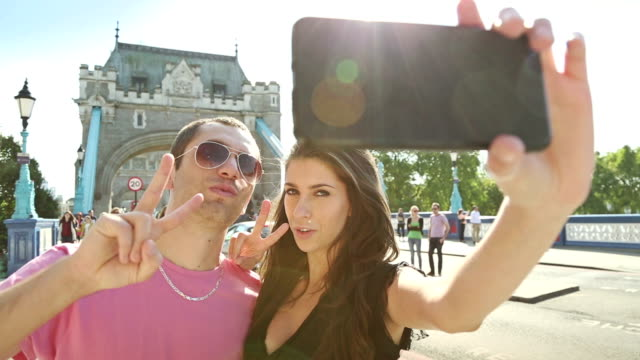 Couple takes a selfie in front of the Tower Bridge