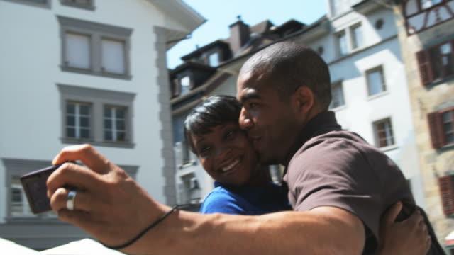 couple taking a photo of themselves - kamerafahrt auf schienen stock-videos und b-roll-filmmaterial
