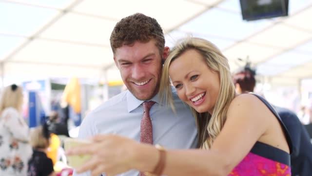 paar unter einem selfie bei den rennen - kopfschmuck kopfbedeckung stock-videos und b-roll-filmmaterial