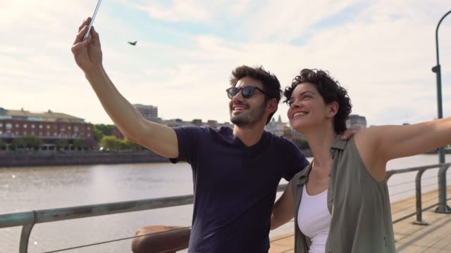 couple taking a selfie in puerto madero - puerto madero stock videos & royalty-free footage