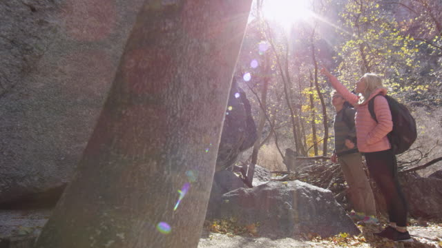stockvideo's en b-roll-footage met couple taking off gear as they prepare to climb boulder - boulder rock