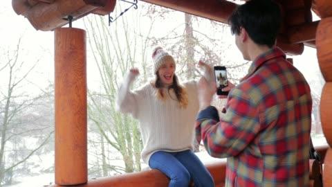 couple taking photos on their ski lodge balcony - ski resort stock videos & royalty-free footage