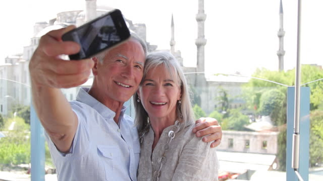 couple taking picture on rooftop in front of the blue mosque, istanbul, turkey - 自分撮り点の映像素材/bロール