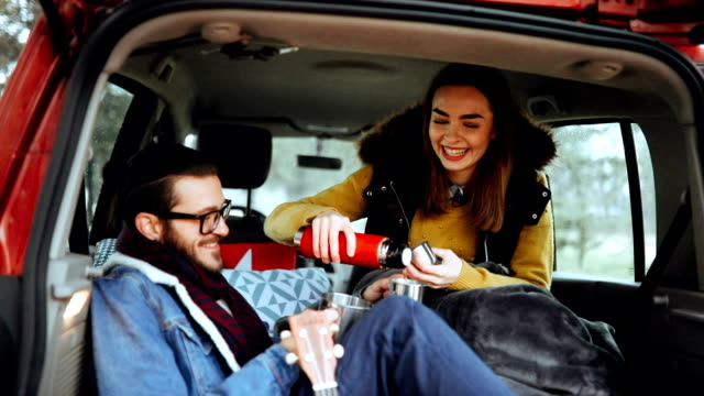Couple taking rest from driving and warming up with hot drinks
