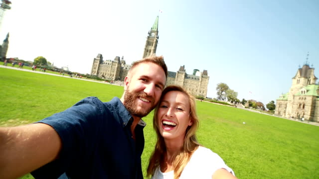 Couple taking selfie in front of Canadian Parliament
