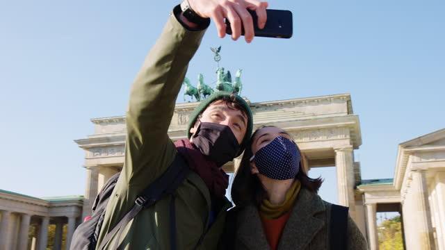 vidéos et rushes de couples prenant le selfie devant la célèbre porte de brandebourg - monument