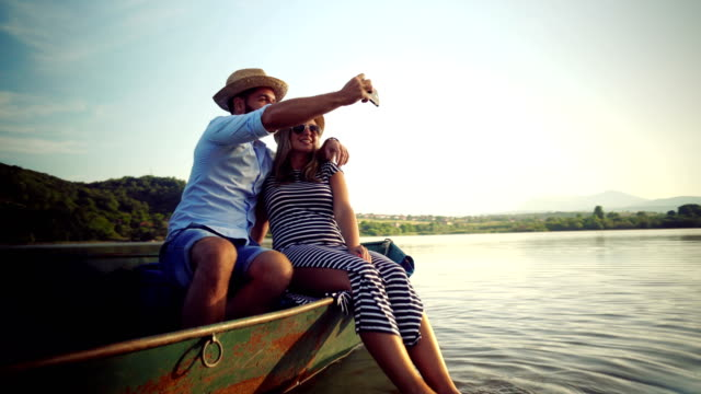 couple taking selfie on a rowboat - photographing stock videos and b-roll footage