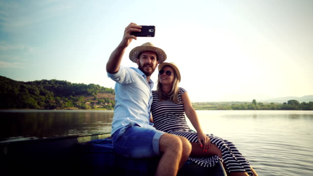 Couple taking selfie on a rowboat