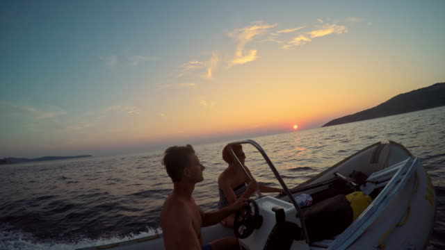 POV Couple taking selfie on motorboat at sunset