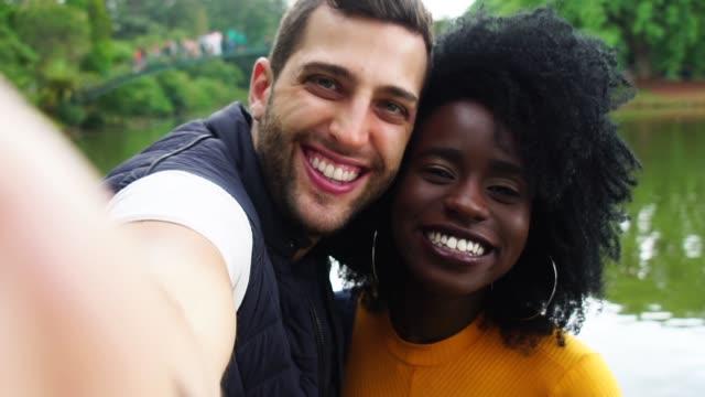 vidéos et rushes de couples prenant des photos de selfie dans le stationnement - élève du secondaire