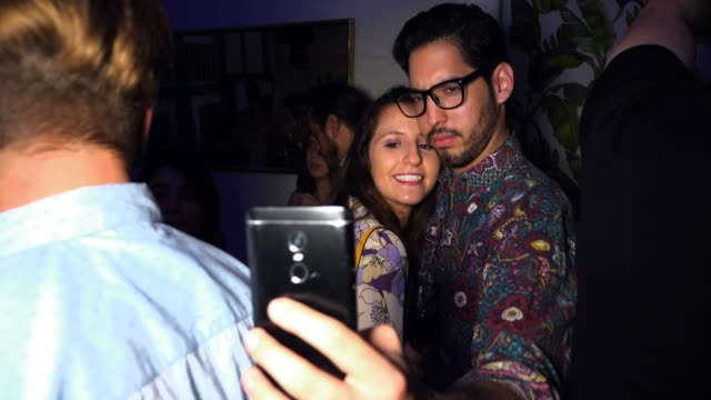 vidéos et rushes de ms couple taking selfie with smart phone during party in night club - flirter