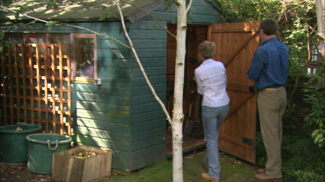 stockvideo's en b-roll-footage met ws couple taking tools out of the shed - 45 49 jaar