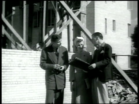 vidéos et rushes de dramatization couple taking w/ agent at construction site agent w/ blueprints saying that's all he has left woman saying it's so small male saying... - 1942