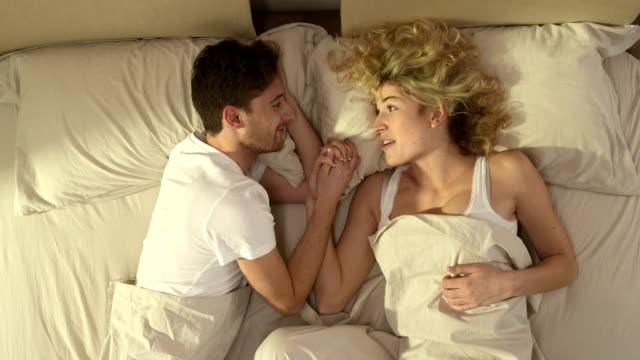Couple parlant et embrassant au lit