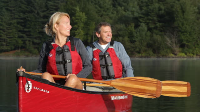 ms couple talking and laughing in canoe on lake / stowe, vermont, united states - stowe vermont stock videos & royalty-free footage
