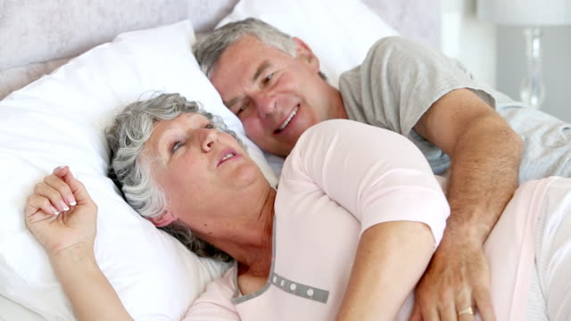 couple talking and laughing in the bed - auf der seite liegen stock-videos und b-roll-filmmaterial