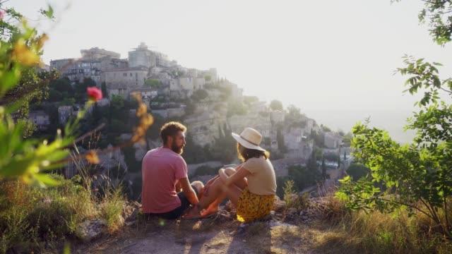 paar im gespräch und blick auf gordes dorf in der provence - region provence alpes côte d'azur stock-videos und b-roll-filmmaterial