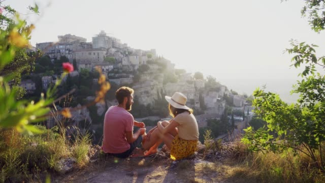 couple talking and looking at gordes village in provence - heterosexual couple stock videos & royalty-free footage