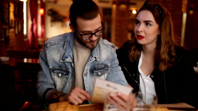 couple talking and looking into menu in a pub - choosing stock videos & royalty-free footage