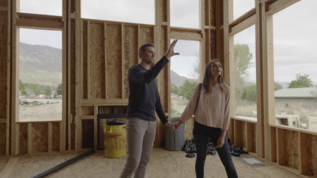 couple talking and pointing in interior of home under construction / pleasant grove, utah, united states - timber stock videos & royalty-free footage