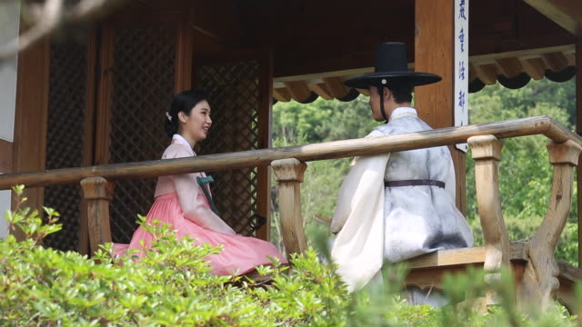 a couple talking and wearing a hanbok (korean traditional clothes) in the gazebo - korean ethnicity stock videos & royalty-free footage