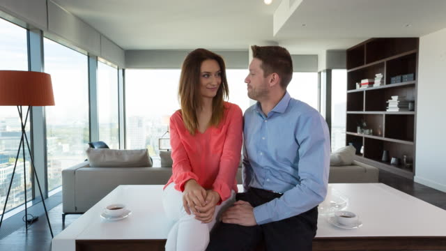 MS couple talking at home in penthouse apartment
