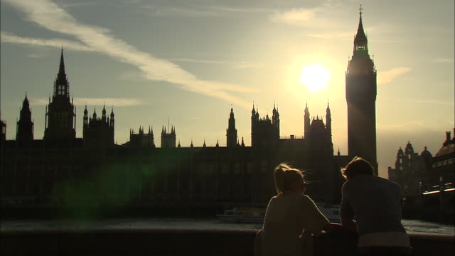 couple talking in front of a backlit silhouette long of big ben in london, england - back lit stock videos & royalty-free footage