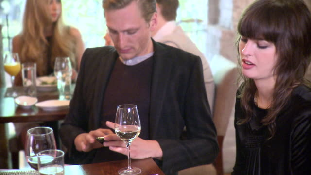 MS Couple talking in restaurant, man showing cell phone to woman, New York City, New York, USA
