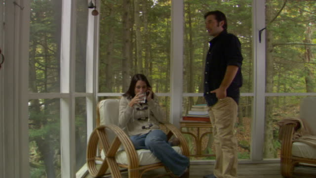 MS, Couple talking on mobile phone on porch of country house, Phoenicia, New York, USA