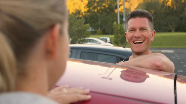 couple talking over the roof of a car in a carpark - parking stock videos & royalty-free footage
