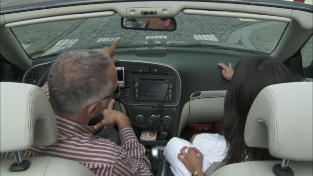vídeos y material grabado en eventos de stock de cu ha couple talking, sitting in convertible car at street crossing, brussels, belgium - indicar