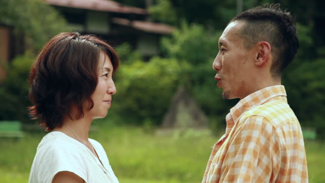 cu couple talking to each other face to face / tokyo, japan - paar mittleren alters stock-videos und b-roll-filmmaterial