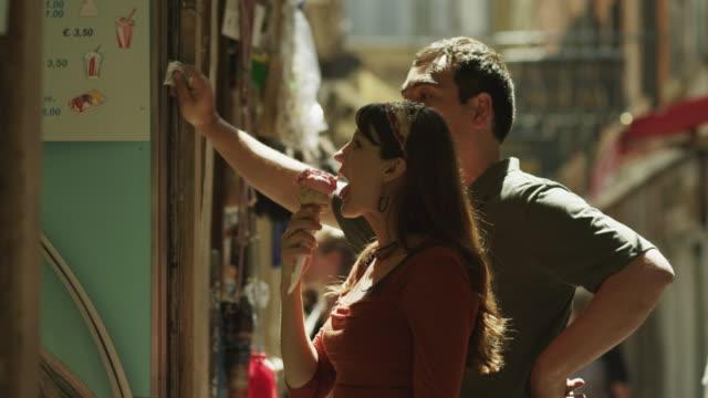 ms couple talking to shop vendor standing on street / venice,veneto - venedig stock-videos und b-roll-filmmaterial